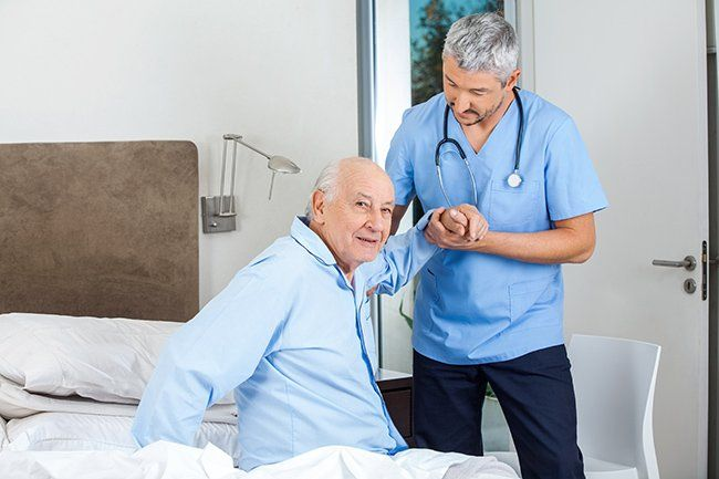 A nurse in blue scrubs helps an elderly man out of bed.