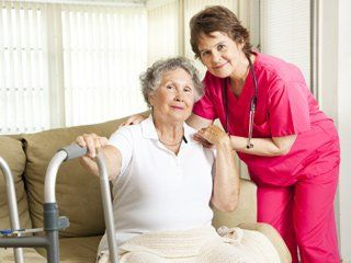 A home care worker helping an elderly woman with a cane down the stairs.