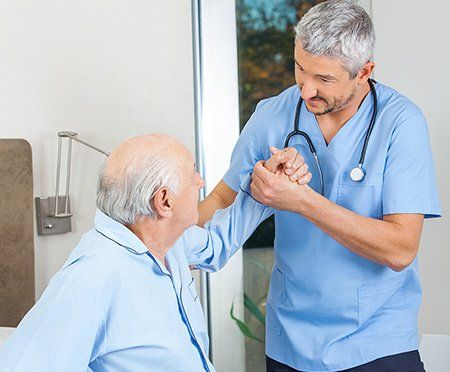 A home health aide helps an elderly man out of bed.