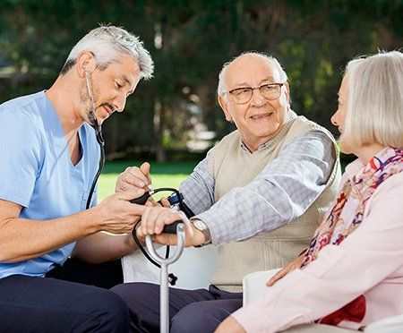 An elderly couple sits in the park while a home health aide takes the man's blood pressure.
